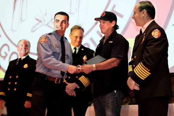 Tyler McKerchie, the youngest among nine newly graduated Seminole Tribe of Florida Fire Rescue Department firefighter-paramedics, receives his badge and certificate from Hollywood Councilman Chris Osceola and Fire Rescue Chief Donald DiPetrillo during the graduation ceremony at Tribe Headquarters.