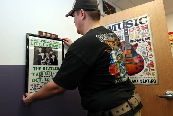 Hard Rock design and installation technician Michael Edgar displays a Beatles poster Aug. 29 at the Hollywood Boys & Girls Club music studio.