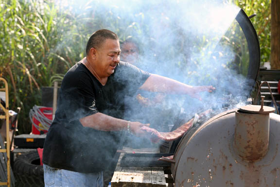 Miguel Cantu puts one of about 40 slabs of ribs on the grill Oct. 10 during the Seminoles in Recovery seventh annual Fish Fry in Trail.