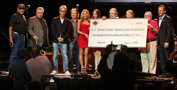 Seminole Hard Rock & Casino Hollywood reps present American Indian Veterans Memorial Inc.   with a check for $120,000 at Hard Rock Live Nov. 12. From left are President Mitchell Cypress, Chairman James E. Billie, Gerry Beckley and Dewey Bunnell from the band America, two Hard Rock girls, AIVMI President Stephen Bowers and his wife, Elizabeth Bates, Roy Murry of AIVMI, and Bill Wright, president of the Hard Rock Hollywood.