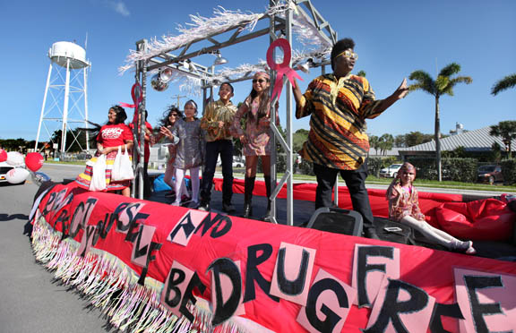 Led by Ahfachkee School music teacher Jania Harden, students sing and dance to Aretha Franklin's 'Respect' during the Big Cypress Red Ribbon Week parade Oct. 20. The theme for this year's Red Ribbon Week was 'Respect Yourself, Be Drug Free.'
