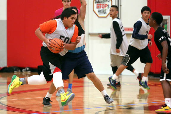Shelby Osceola tries to pass Ethan Cypress Oct. 24 during the high school division championship game in the second annual Ballin' for a Cause Youth Basketball Tournament at the Howard Tiger Recreation Center in Hollywood.