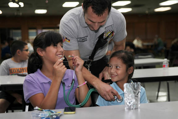 Alyssa Bowers and Maya Bowers learn to use a stethoscope from firefighter Vasile Mircea at the Nov. 17 Police Explorers meeting.