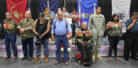Seminole Tribe veterans display reverence while 'Taps' is played to honor veterans who have passed on. The event attracted nearly 100 tribal and non-tribal veterans and loved ones.