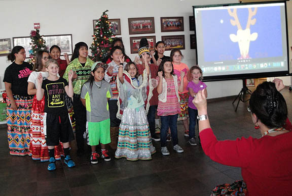 Pemayetv Emahakv Charter School students sing Christmas carols Dec. 1 to children from Real Life Children's Ranch residential group home during a holiday party in the school cafeteria.