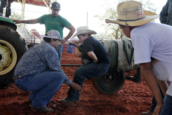 Ivan Bruised Head shows Creek Gopher, 11, how to use the steer saver machine to practice his chute dogging technique at the EIRA rough stock clinic Jan. 9 in Big Cypress.
