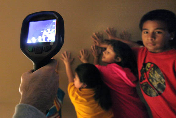 Big Cypress children place their hands on a wall while a thermal imaging camera held by a Seminole Tribe of Florida Fire Rescue Department firefighter detects only their body heat.