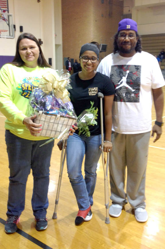 Okeechobee High School senior Lahna Baker is joined by her parents, Mona and Preston Baker, during the girls basketball team's senior night Jan. 21. Lahna was honored during a pregame ceremony but did not play due to an injury.