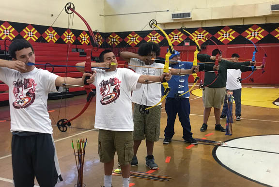Middle school boys at Pemayetv Emahakv Charter School participate in a virtual archery tournament in late February at the Brighton gym.