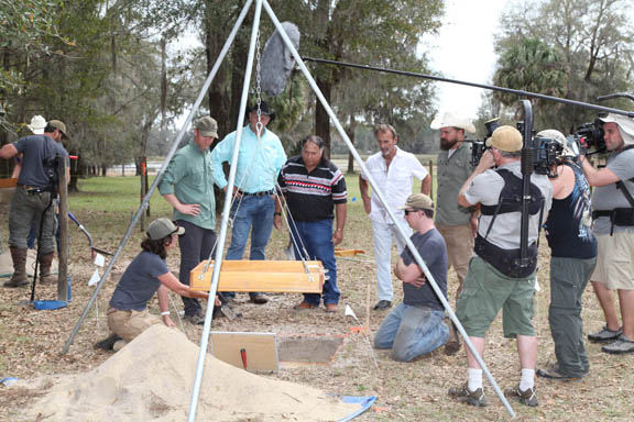 At one of several Bowlegs Town excavations, an archaeology team, with tribal historian and Seminole Chief Justice Willie Johns, fourth from left, is filmed by Committee Films March 12 for a future History Channel documentary.