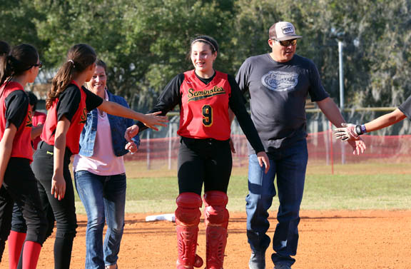 Pemayetv Emahakv Charter School catcher Jacee Jumper is escorted past her teammates by Jo Jumper, left, and Naha Jumper during the team's eighth-grade parent night ceremony March 7 in Brighton.