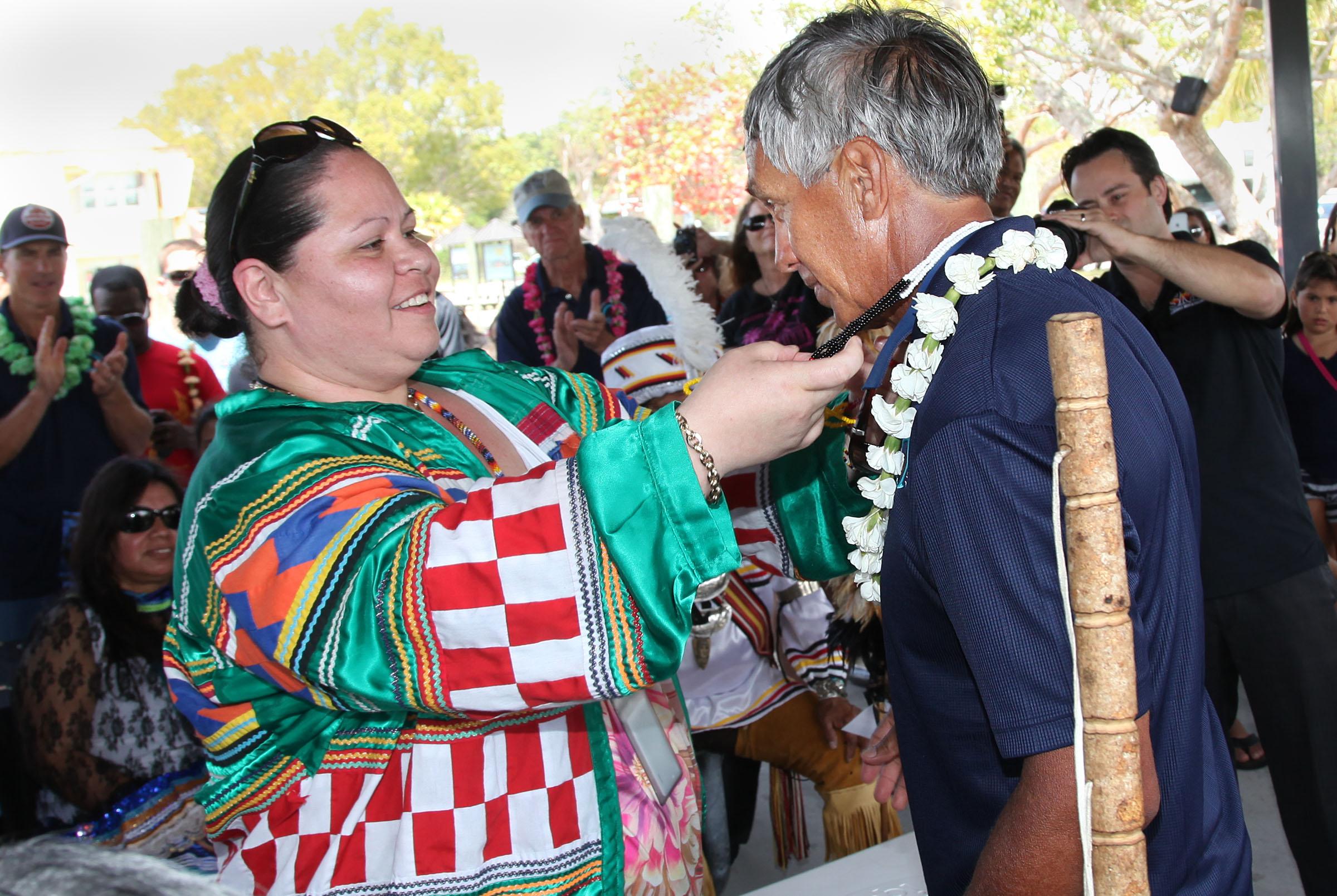 Chairman James E. Billie's Executive Assistant Trishanna Storm bestows a gift of Seminole medicine beads to Hawaiian canoe Captain Nainoa Thompson.