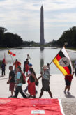 Carrying the Seminole Tribe of Florida flag, We Do Recover members Kenny Tommie, Charlie Tiger and Christopher Billie arrive at the Lincoln Memorial Reflecting Pool, with the Washington Monument in the background, for the Longest Walk 5 event July 15, which marked the end of the 3,600-mile journey across the country.