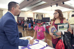 Joshua Arce, acting Dean of Students for Haskell Indian Nations University, gives information to Erica Frank, 29, about scholarships, campus life, and the application process at the Education Expo.