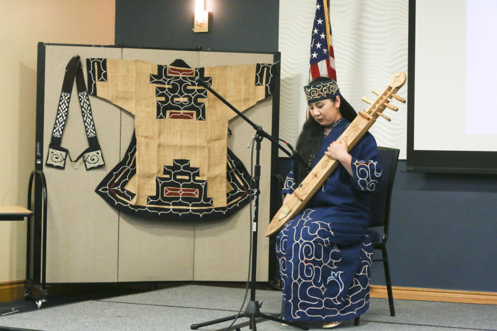 Fukiko Goukon, of the Ainu people, plays the Tonkori instrument, which plays like a harp, in front of a large audience at Florida International University. (Stephanie Rodriguez photo)
