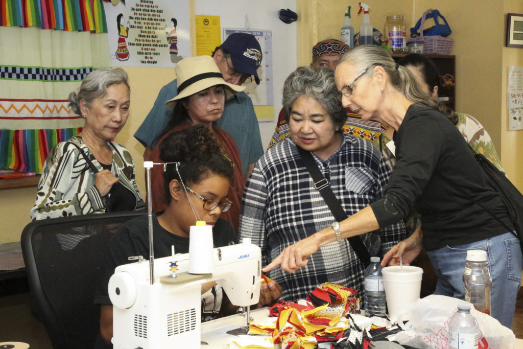 Masako Kubota, left, FIU instructor for the Asian Studies Program and Department of Modern Languages, stands with members of the Ainu people while they watch a sewing demonstration from Nuthkee Henry with guidance from retired nurse wife Felicia Wiedman, wife of FIU instructor Dennis Wiedman, during the Ainu's visit to the Brighton Reservation on Nov. 7. (Stephanie Rodriguez photo)