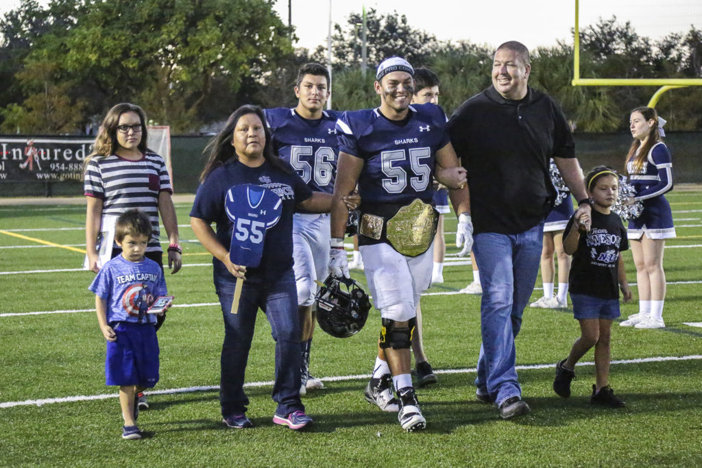 University School senior Brady Latchford (55) is joined by his parents, Amy Latchford and Seminole Police Chief William Latchford, brother and teammate Bradley (56), and other family members during the team's senior night ceremony Nov. 4 in Davie. (Stephanie Rodriguez photo)