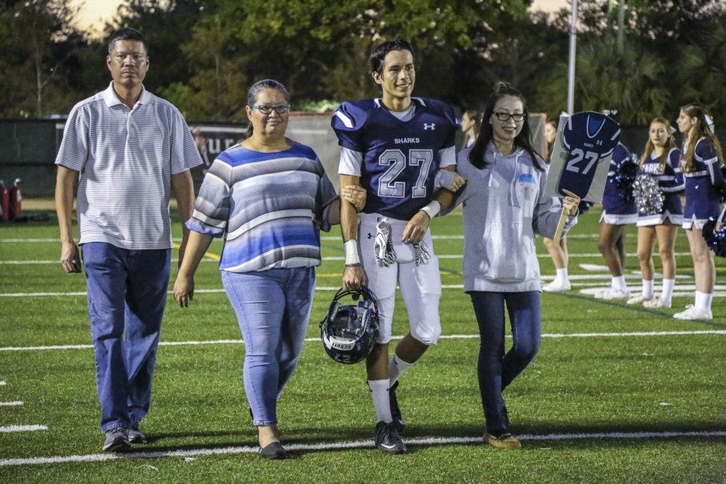 Rhett Tiger is joined by his parents, Elrod Bowers and Holly Bowers, and younger sister Katie Young during University School's senior night ceremony Nov. 4 in Davie. (Stephanie Rodriguez photo)