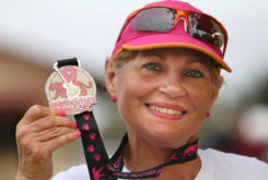 Elia Mendez, of Miami, shows off her 5K medal Oct. 30 after running in the Pink Panther Prowl, a 5K and 10K run, walk, or stroll through the Big Cypress. (Eileen Soler photo)