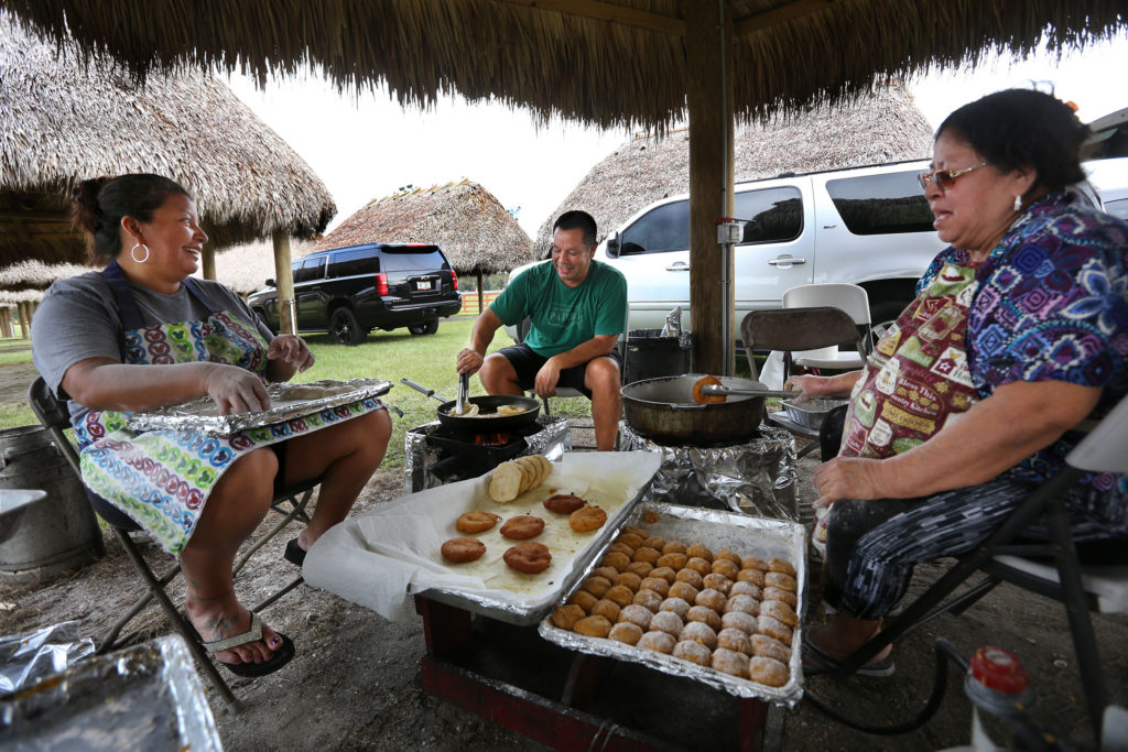 Trisha Osceola, Marcellus Osceola, and Mary Jo Micco pitch in at the Pink Panther Prowl to provide a taste of hospitality Seminole style - free fresh pumpkin and plain frybread. (Eileen Soler photo)