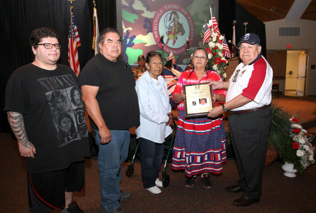 Stephen Bowers, at far right, presents a plaque commemorating Sammy Gopher's military service to his sister Beulah Gopher Nov. 3 during the Brighton Veterans Day event. Also pictured are, from left, Alyxter Loudermilk, Daniel Gopher and Madeline Tongkeamha.(Beverly Bidney photo)