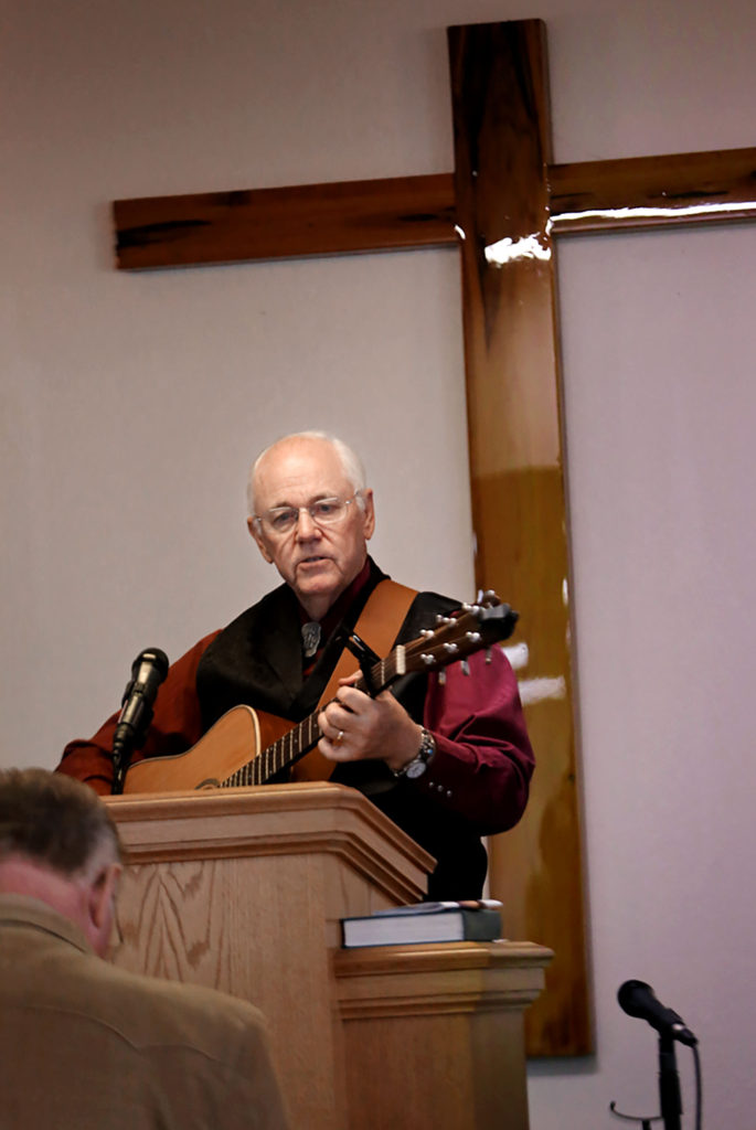 """Pastor Arlen Payne opens the 50th anniversary celebration service for Big Cypress New Testament Baptist Church on Dec. 3 with a rousing rendition of """"I'll Fly Away."""" (Eileen Soler photo)"""