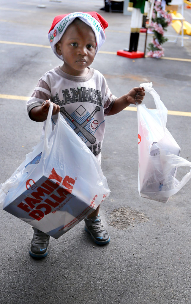 A youngster brings bags of toys to donate to the Seminole Tribe's toy drive next to the Seminole Classic Casino in Hollywood. (Eileen Soler photo)