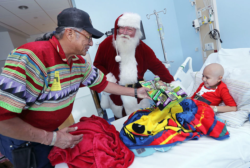 President Mitchell Cypress and Santa Claus surprise a young patient with a Christmas present Dec 6 at Joe DiMaggio Children's Hospital in Hollywood. (Eileen Soler photo)