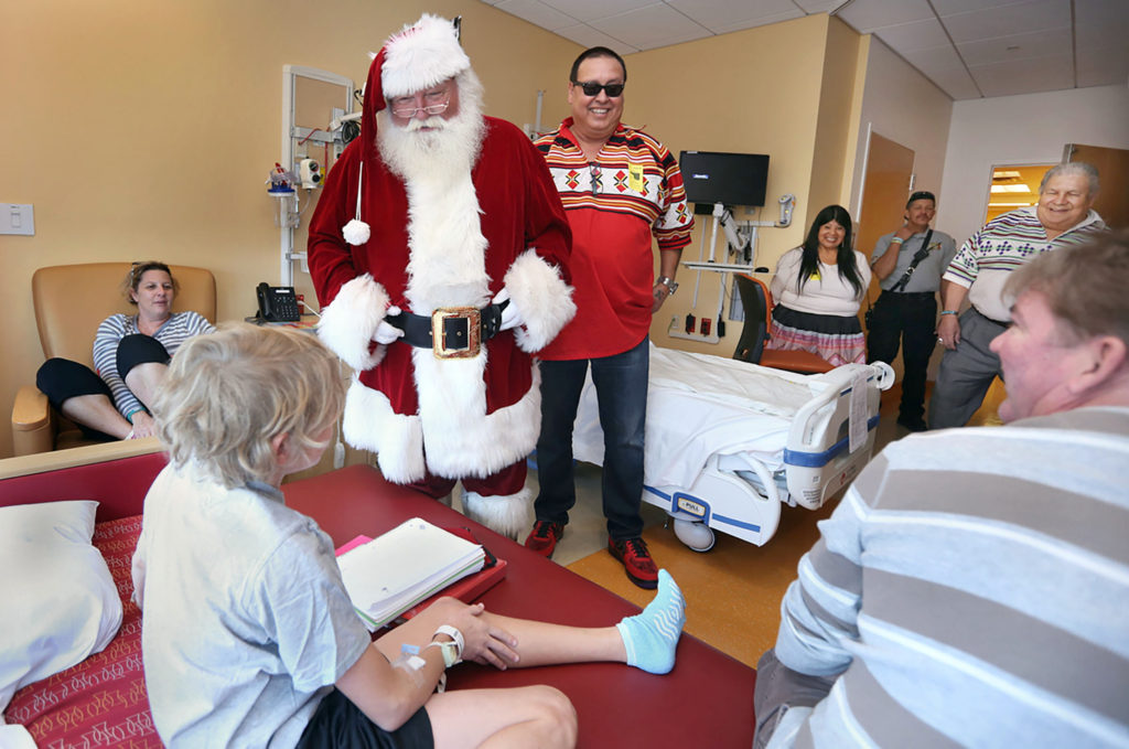Santa Claus, Trail Liaison Norman Huggins and other Seminole Tribe representatives make a personal visit to Joe DiMaggio Children's Hospital patient Brendan Gondek, 11, of Hallandale, during a surprise holiday toy giveaway Dec. 6. (Eileen Soler photo)