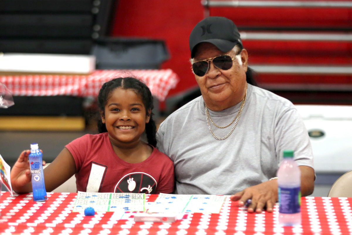 Mohayla Billie, 8, plays Bingo with her grandfather Thomas Billie at the Big Cypress Father's Day event June 18. (Beverly Bidney photo)