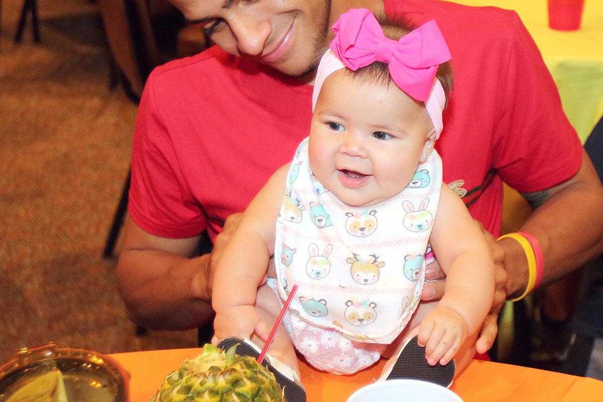 """Uncle"" Eddy Gonzalez holds Evianna Nunez during the luncheon. (Damon Scott photo)"