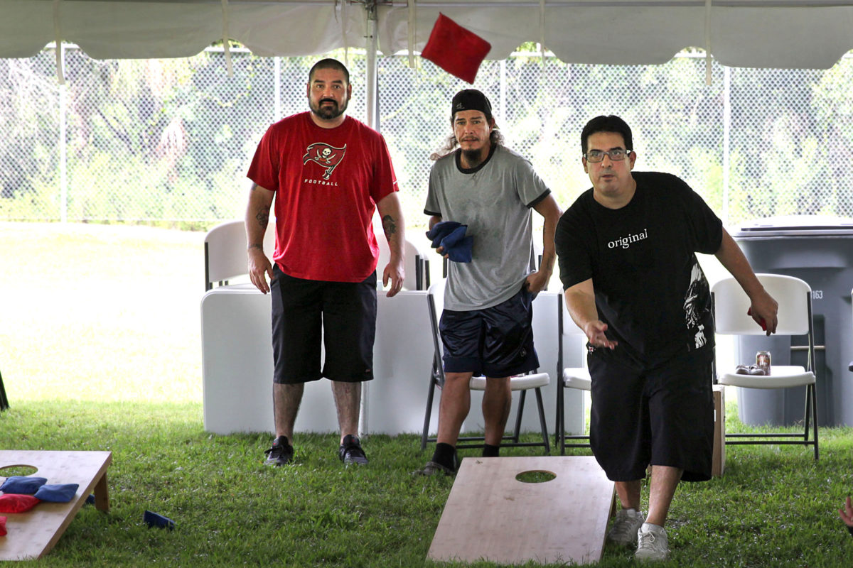 Michael Alvarado and Gil Yzaguirre watch to see if the beanbag thrown by Alan McInturff hits the mark at the Immokalee Father's Day celebration. (Beverly Bidney photo)