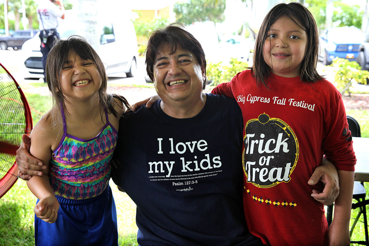 Johnny Jimmie, center, is flanked by two of his 12 children, Holama and Alice Jimmie as they enjoy the Immokalee Father's Day party. (Beverly Bidney photo)