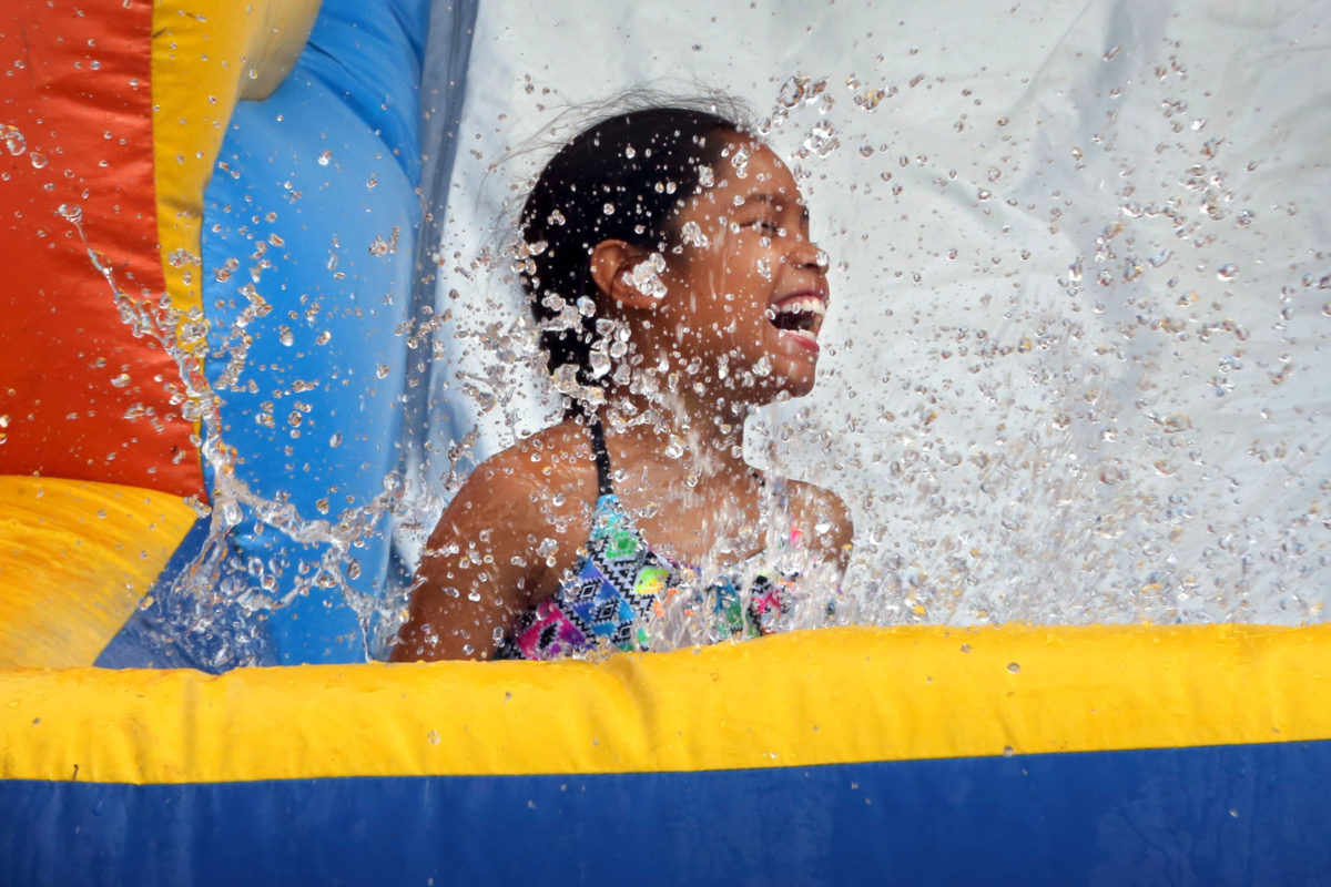 Jazmine Garcia gets lost in the splash of the water slide during the Immokalee summer camp kickoff water fun day. (Beverly Bidney photo)