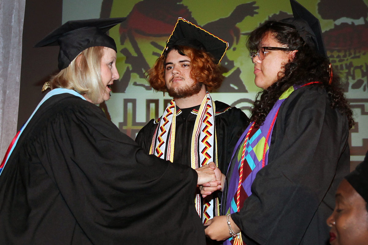 Ahfachkee School Principal Dorothy Cain congratulates Elisah Billie and Eyanna Billie during the school's graduation May 24 at the Herman Osceola Gym in Big Cypress. (Beverly Bidney photo)