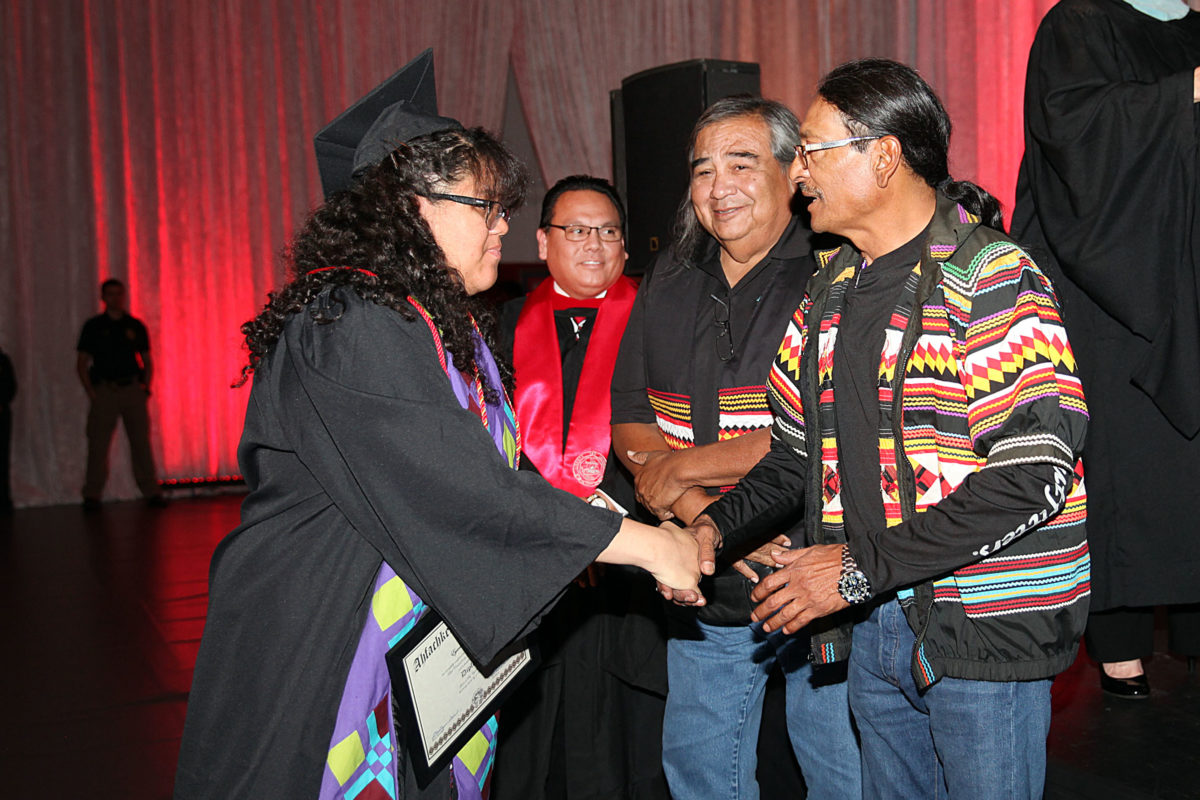 After receiving her high school diploma, Eyanna Billie shakes hands with Big Cypress Councilman Mondo Tiger with Big Cypress Board Rep. Joe Frank and Executive Director of Administration Lee Zepeda among the well-wishers. (Beverly Bidney photo)