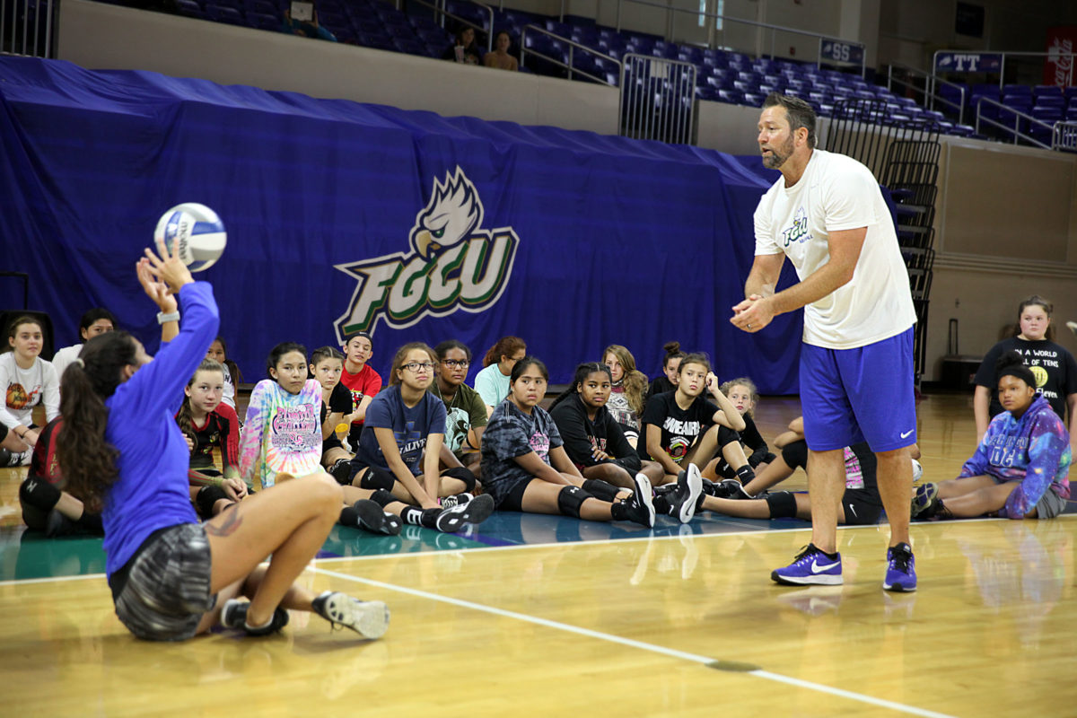 FGCU volleyball coach Matt Botsford shows the group how to line up behind the ball to return it, even if it means leaning a lot. (Beverly Bidney photo)