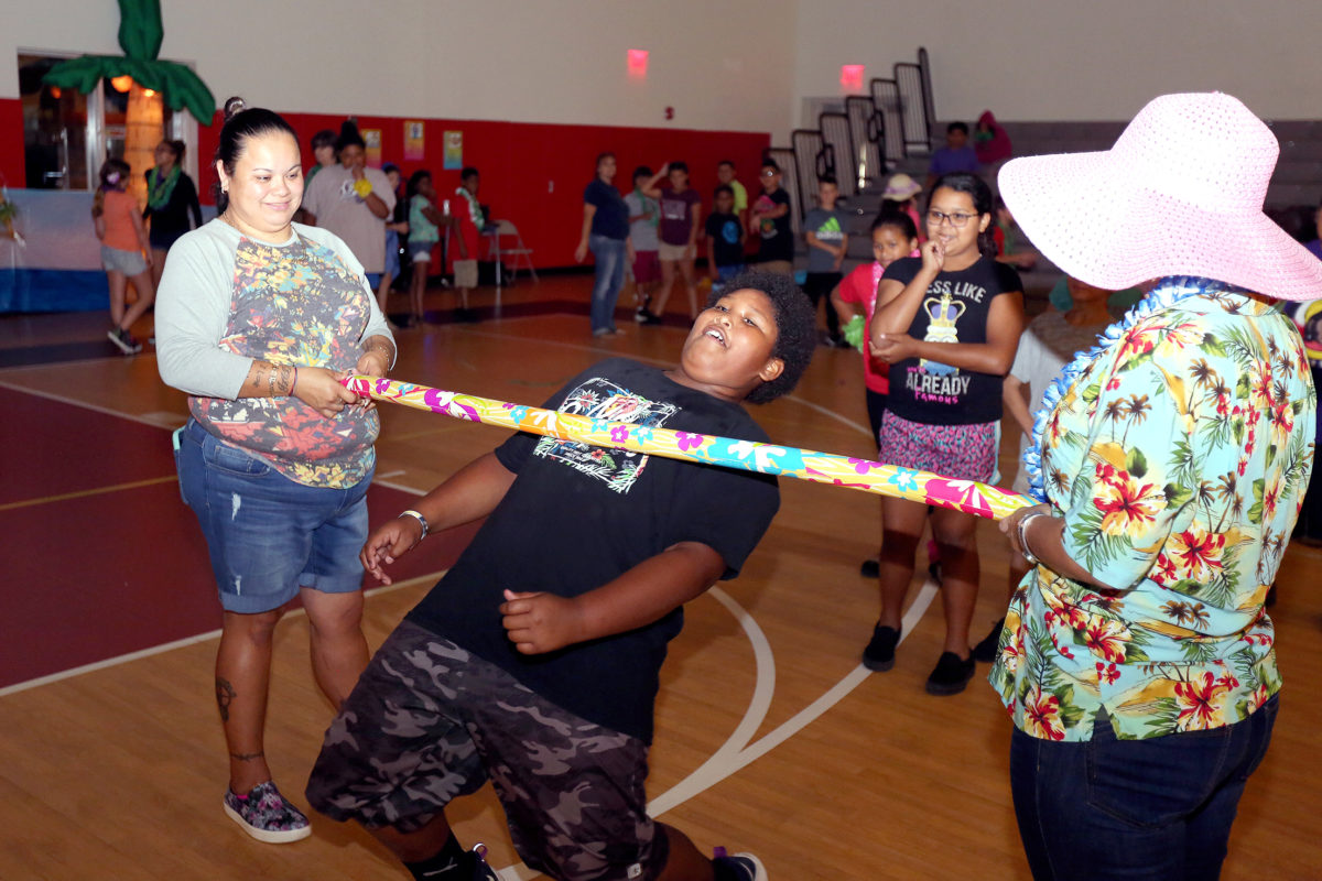 Students go low in the limbo line at PECS. From left to right are Jimi Jamison, student Adarius Ford and Jade Osceola. (Damon Scott photo)